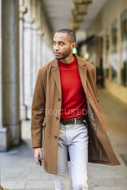 Fashionable young man wearing red pullover and brown coat walking along arcade — Stock Photo