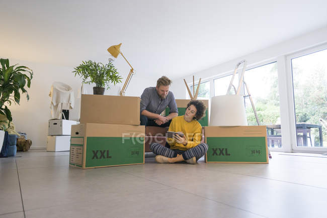 Couple sitting in living room with cardboard boxes using tablet — Stock Photo