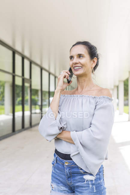 Ritratto di donna matura sorridente al telefono all'aperto — Foto stock