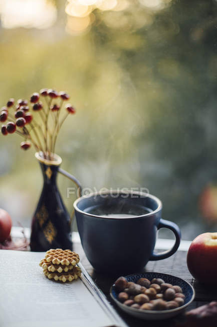 Cup of steaming tea, book, cookies and autumnal decoration on window sill — Stock Photo