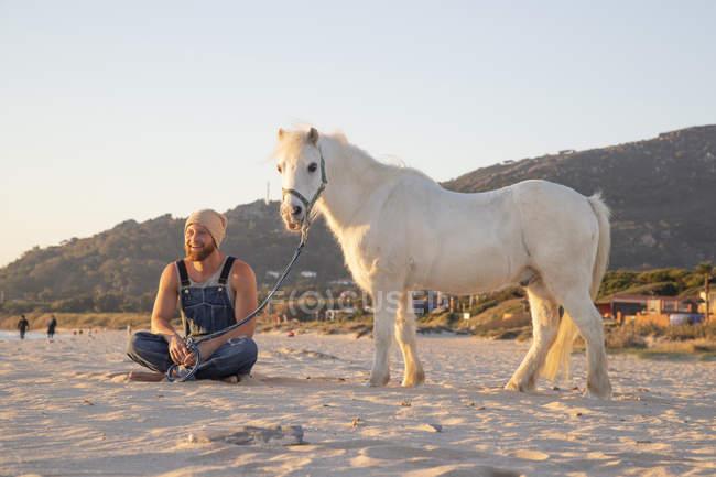 Испания, Фауфа, счастливый человек с пони, сидящий на пляже — стоковое фото