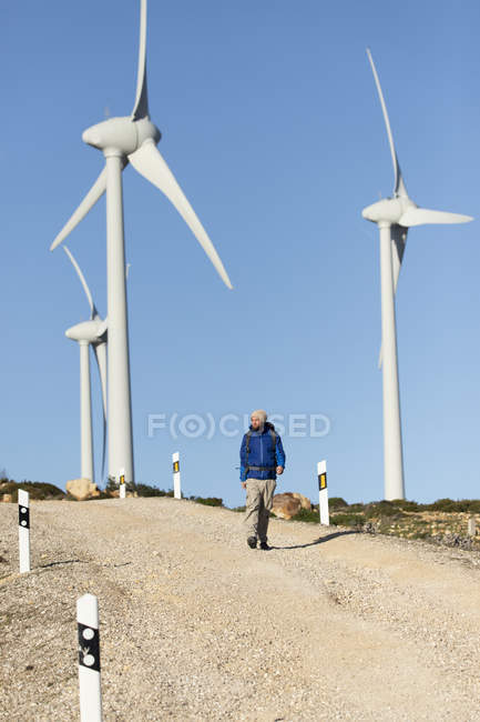 Spain, Andalusia, Tarifa, man on a hiking trip walking on dirt road surrounded by wind turbines — Stock Photo