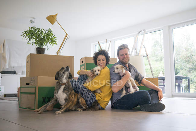 Happy couple sitting in living room with dogs and cardboard boxes — Stock Photo