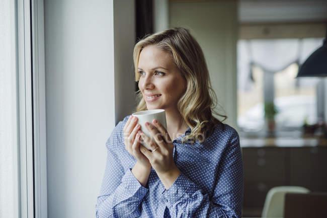 Mulher sorridente segurando uma xícara de café na janela em casa — Fotografia de Stock