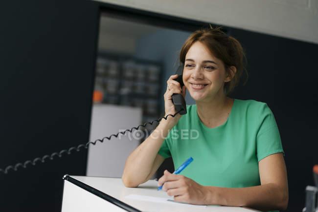 Mulher sorridente falando no celular no escritório — Fotografia de Stock