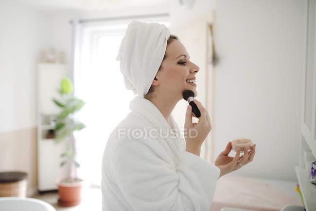 Femme souriante en peignoir appliquant maquillage le matin à la maison — Photo de stock