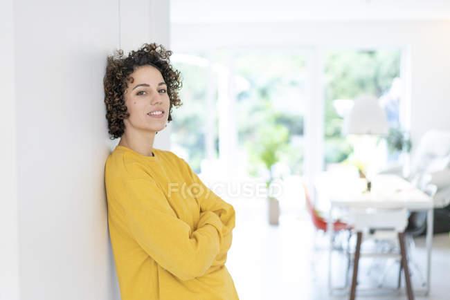 Retrato de mulher encostada a uma parede em casa — Fotografia de Stock