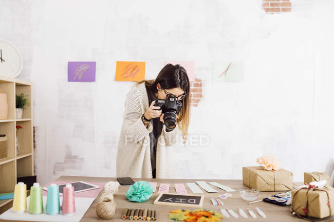 Young woman taking pictures with a camera for her craft blog — Stock Photo