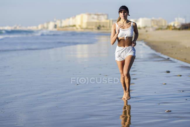 Femme sportive courant sur la plage — Photo de stock