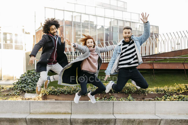 Three happy friends jumping in the city — Stock Photo