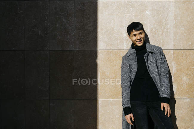 Portrait of fashionable young man wearing black turtleneck pullover and grey coat — стокове фото