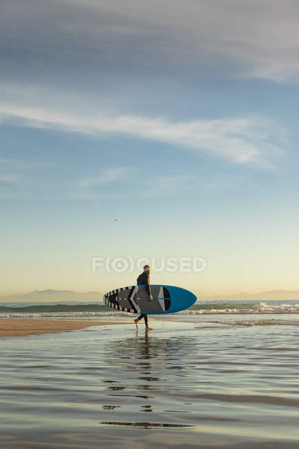 Spanien, Andalusien, Tarifa, Mann geht mit Stand Up Paddle Board am Strand — Stockfoto