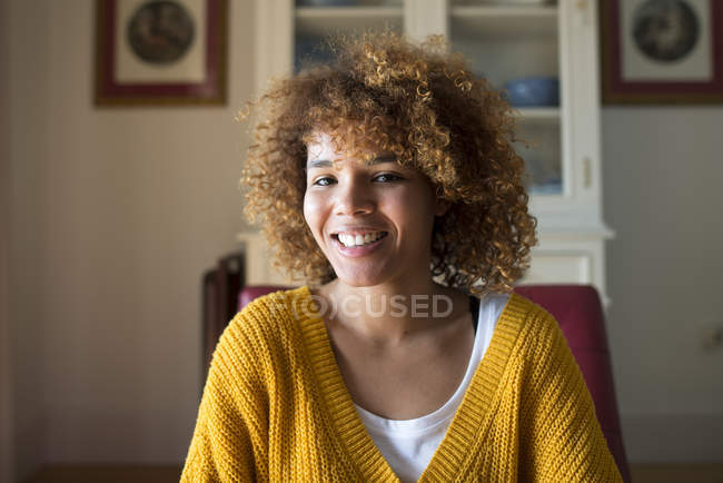 Portrait of smiling young woman with curly hair at home — Stock Photo