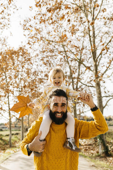 Father carrying his little daughter on shoulders in the morning in a park in autumn — Stock Photo