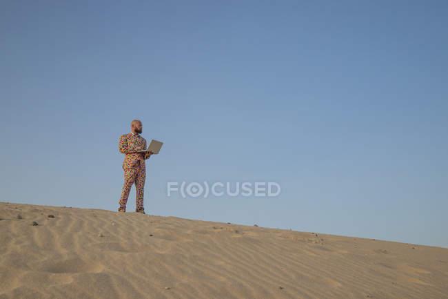 Человек с ноутбуком в костюме с красочными горошинками стоит на песчаной дюне и смотрит на расстояние — стоковое фото