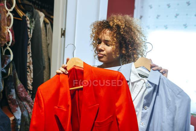 Молода жінка з кучерявим волоссям дивиться на одяг у своєму шафі. — стокове фото