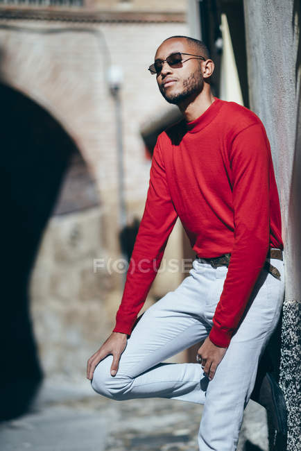 Портрет модного молодого человека в красном свитере и носках, наслаждающегося солнечным светом — стоковое фото