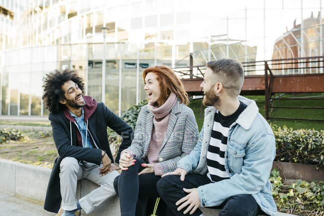 Троє щасливих друзів говорять у місті. — стокове фото