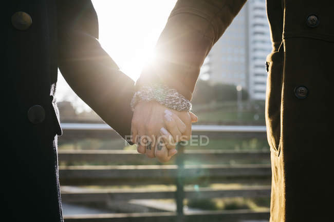 Close-up of couple holding hands in backlight — Stock Photo