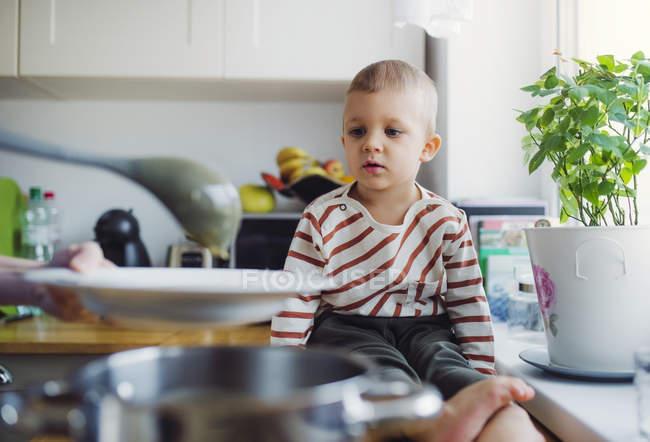 Criança menino assistindo mãe preparando comida na cozinha em casa — Fotografia de Stock