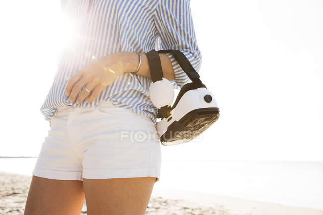 Wman with virtual reality glasses on the arm, at the beach against the sun — Stock Photo