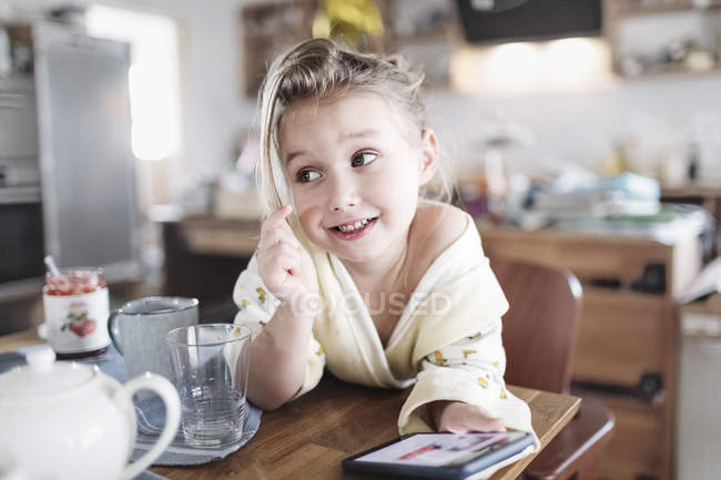 Portrait of smiling little girl with smartphone in the kitchen — Stock Photo
