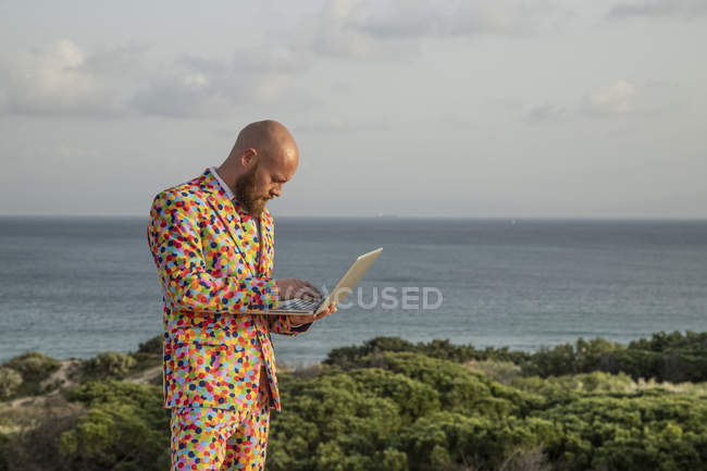Мужчина в костюме с красочными горошинками на открытом воздухе — стоковое фото