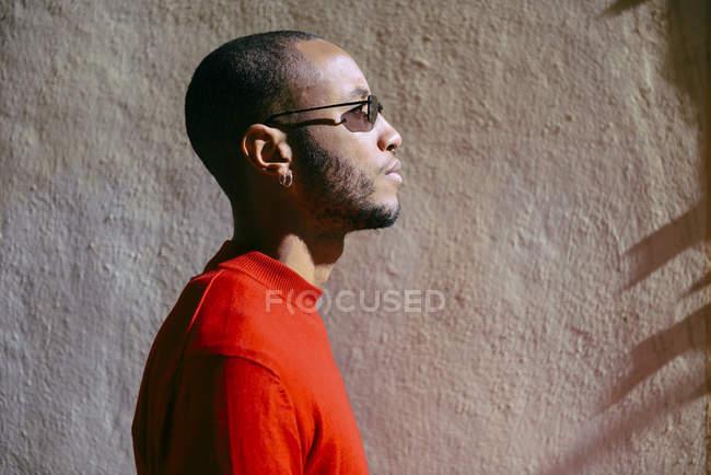 Perfil del joven que usa gafas de sol y pulverizadores rojos a la luz del sol - foto de stock