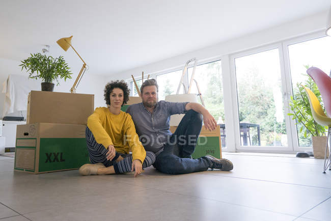 Portrait of couple sitting in living room with cardboard boxes — Stock Photo