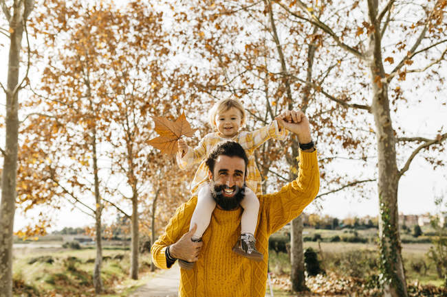 Father carrying his little daughter on shoulders on a morning day in the park in autumn — Stock Photo