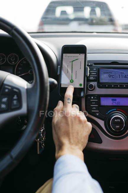 Primer plano del hombre con coche de conducción a mano tatuado utilizando el teléfono celular como sistema de navegación - foto de stock