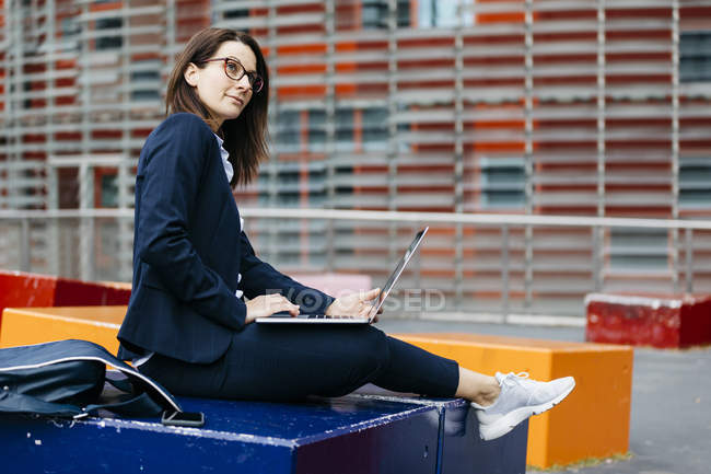 Businesswoman sitting outside office building in the city using laptop — стокове фото