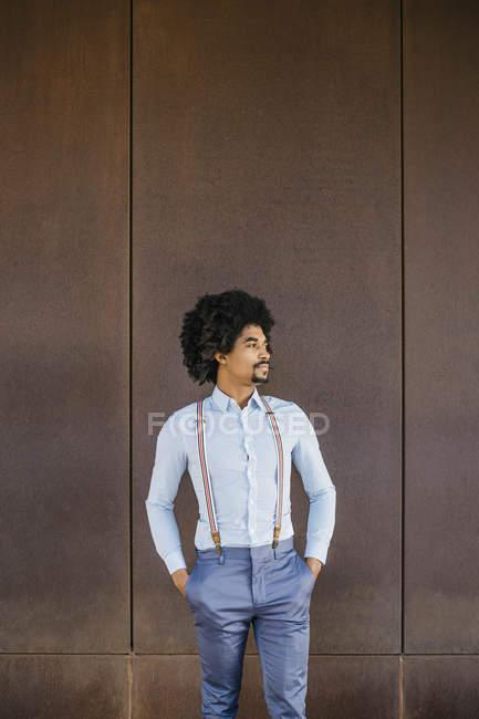 Стоящий перед ржавым фоном мужчина в рубашке и подтяжках — стоковое фото