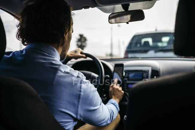 Empresario que conduce el coche usando el teléfono celular como sistema de navegación - foto de stock
