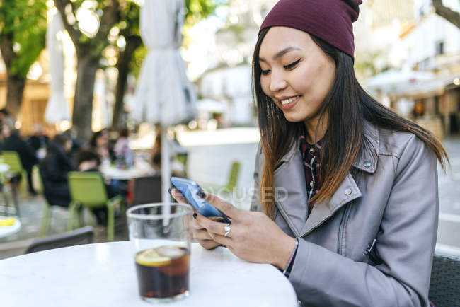 Sorridente giovane donna utilizzando smartphone al caffè marciapiede — Foto stock