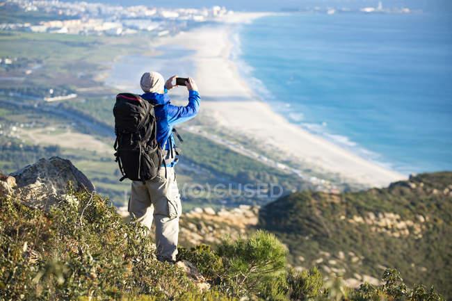 Espagne, Andalousie, Tarifa, homme en randonnée sur la côte prendre une photo de téléphone portable — Photo de stock