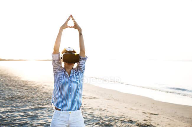 Femme blonde faisant des exercices de yoga sur une plage en thailand avec lunettes de réalité virtuelle 3D — Photo de stock