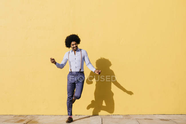 Smiling man dancing in front of yellow wall — Photo de stock