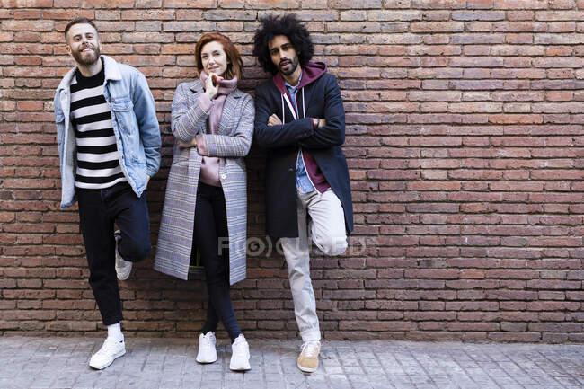 Portrait de trois amis debout devant un mur de brique — Photo de stock