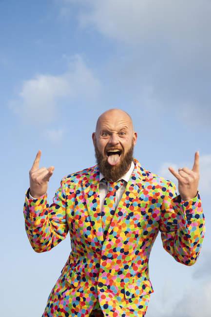Ritratto di uomo calvo con barba che indossa un completo con pois colorati che spuntano dalla lingua — Foto stock