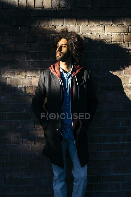 Porträt eines jungen Mannes, der im Schatten an einer Ziegelmauer steht — Stockfoto