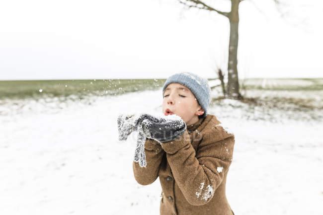 Ragazzo che gioca con la neve in inverno — Foto stock