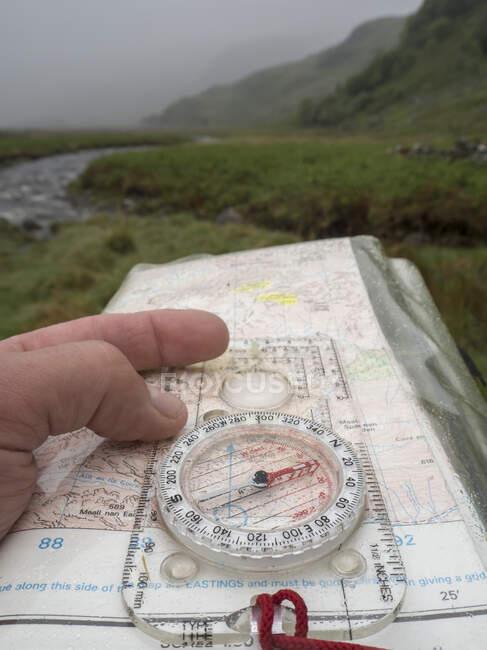 Gran Bretagna, Scozia, Penisola di Knoydart, bussola portatile e mappa durante la pioggia — Foto stock