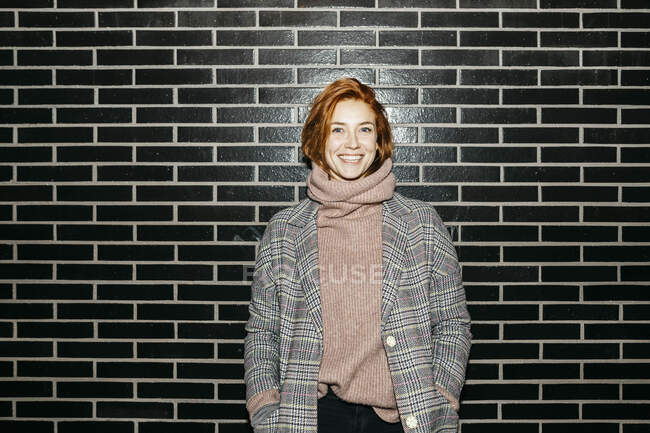 Portrait of a happy young woman standing at a black wall — Stock Photo