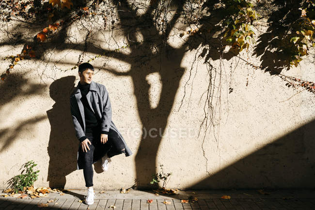 Relaxed young man leaning against wall in autumn — Stock Photo