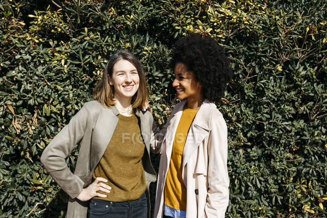 Portrait of two happy women in front of a hedge — Stock Photo
