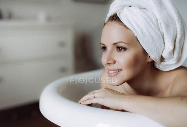 Mulher sorridente com toalha ao redor da cabeça tomando banho em casa — Fotografia de Stock