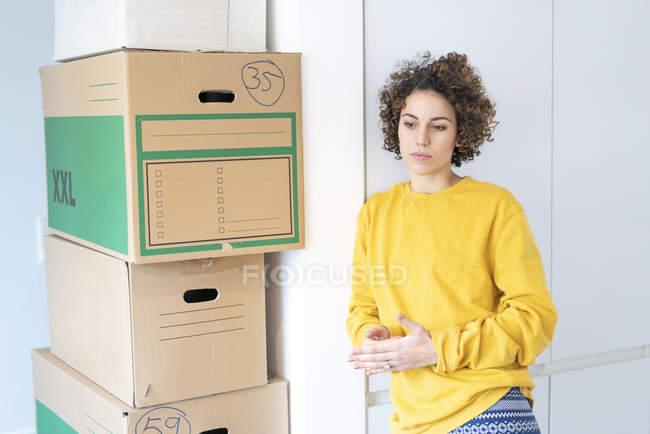 Серьезная женщина дома с картонными коробками — стоковое фото