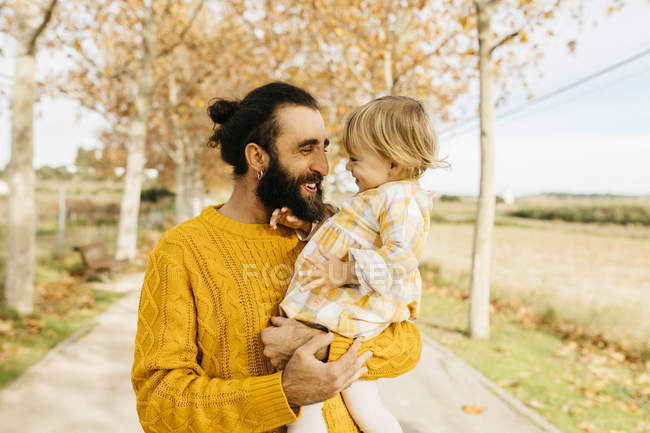 Father carrying his daughter on a morning day in the park in autumn — Stock Photo