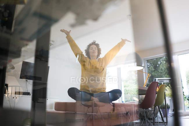 Femme assise sur le canapé à la maison dans la pose de yoga — Photo de stock